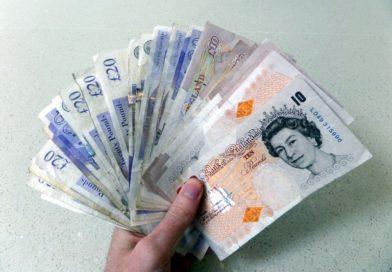 A hand holding British money